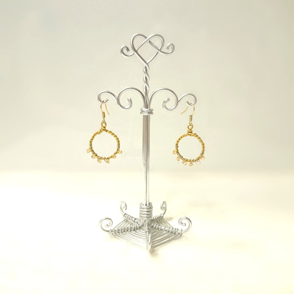 Twisted hoop earrings  with Swarovski crystal, hung on our earring holder. Earrings in gold. Holder in silver.