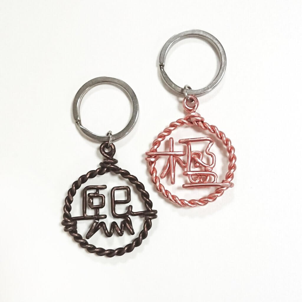 Keychain with Chinese character / Kanji in twisted hoop. In dark bronze / rosegold.