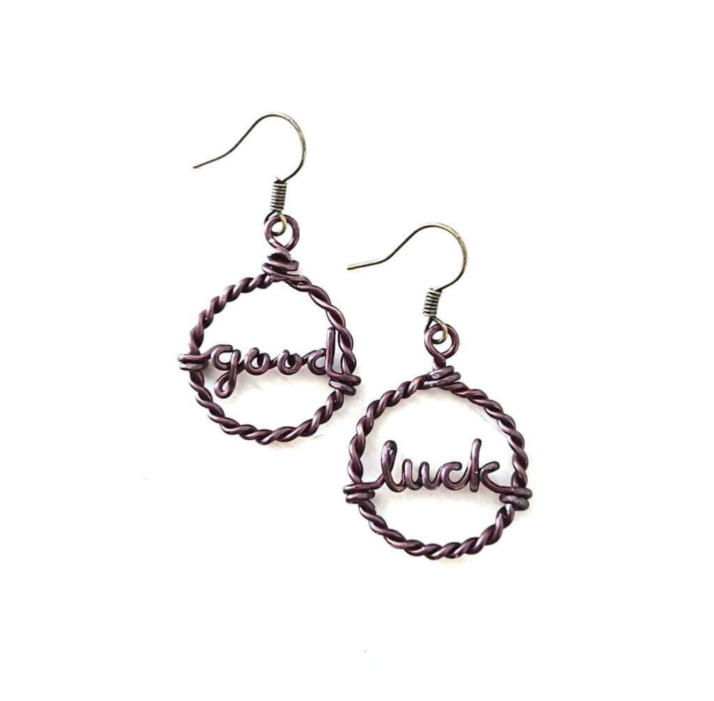 Twisted hoop earrings with customized words. In dark bronze, aluminium.