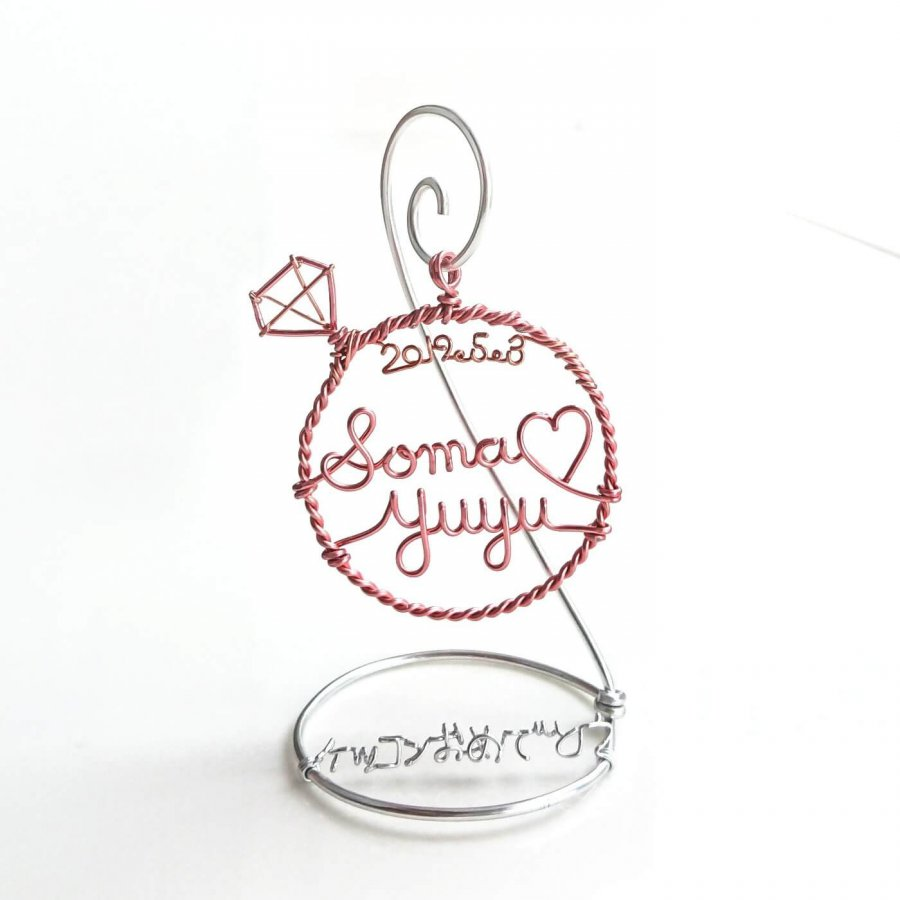 Diamond ring stand with couple names and date.
